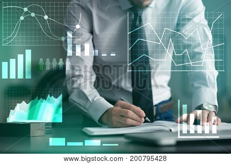 Man writing in notebook at table. Management concept