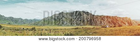 Stunning panoramic landscape of Altai mountains near river Katun and Kuyus district Russia: native grasses meadows lit by sun hills in distance teal sky partly clouded
