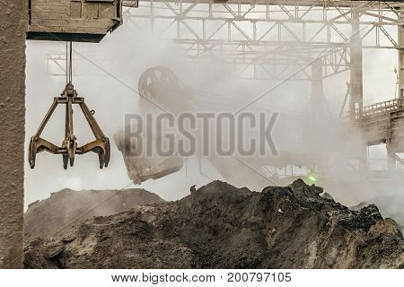 Industrial background. Loading equipment in hot slag dust of heavy metallurgical industry. Excavator and grapple grab of overhead crane in a dirty outdoors industrial plant shop.