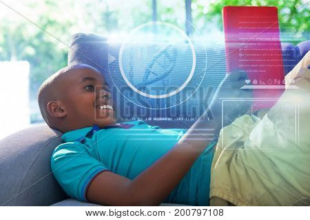Composite image of DNA helix against side view of smiling boy lying while reading novel on sofa at home