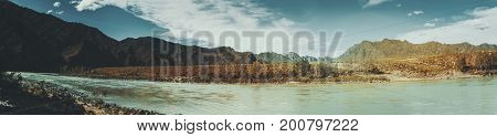 Panorama of Katun river from stony coastline near Kuyus district Altai mountains Russia: shore with grass rocks birch and pine trees fast water current hills in distance teal sky