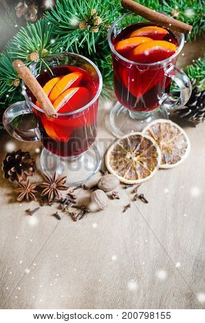 Two Glasses with Mulled Wine Spices and Christmas Tree Branches on wooden background. Drawn Snow Falling Effect. Christmas Postcard. Selective Focus.