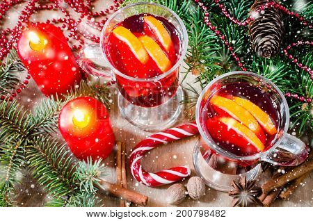 Two Glasses with Mulled Wine Red Candles Spices and Christmas Tree Branches on wooden background. Vintage Toned and Drawn Snow Falling Effect. Selective Focus. Top View
