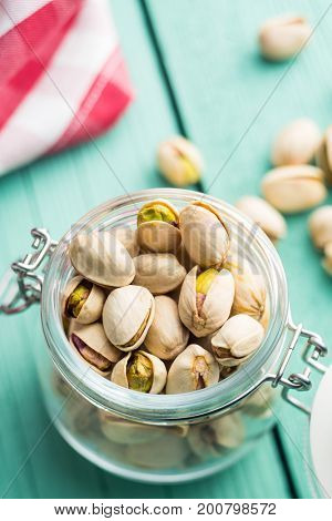 Dried pistachio nuts in jar on kitchen table. Pistachio kernel.