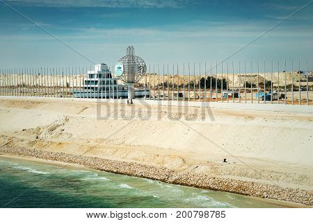 Sinai, Egypt - April 2nd, 2016: Section of the new Suez expansion canal opened in August 2015 with the Suez Canal monument and a government building in the form of a ship