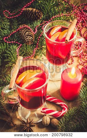 Two Glasses with Mulled Wine Red Candles Spices and Christmas Tree Branches on wooden background. Vintage Toned. Selective Focus.