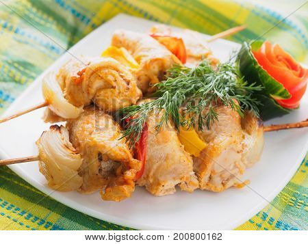 Chicken kebab with vegetables on the plate.