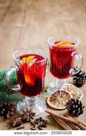 Two Glasses with Mulled Wine Spices and Christmas Tree Branches on wooden background. Christmas Postcard. Selective Focus.