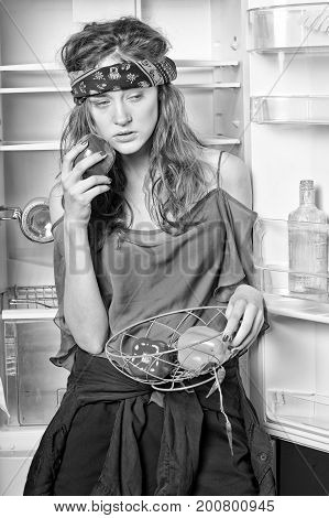 Woman with sweet peppers standing at fridge with open door in kitchen black and white. Healthy food and dieting concept.