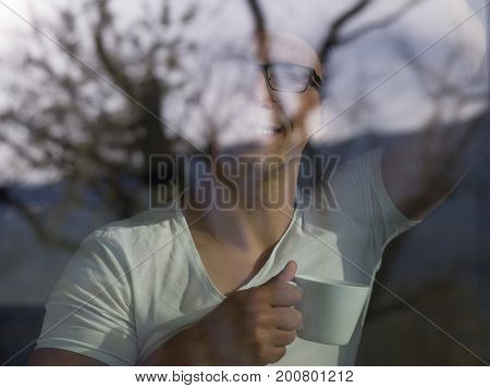young handsome man drinking morning coffee by the window in his home
