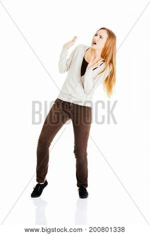 Beautiful casual woman is crouching from sth heavy above her.