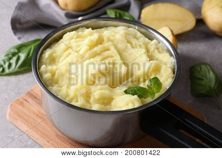 Pot with mashed potatoes on table, closeup