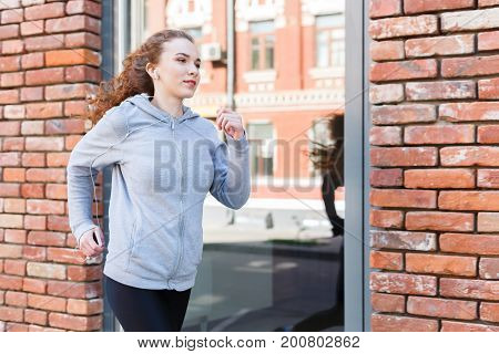 Young redhead woman running in city near brick building with mirror windows, copy space