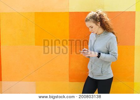 Woman choose music to listen in her mobile phone during jogging in city, copy space, colorful background