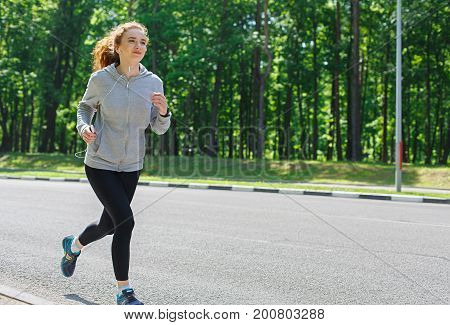 Young sporty woman running on road during morning workout, copy space