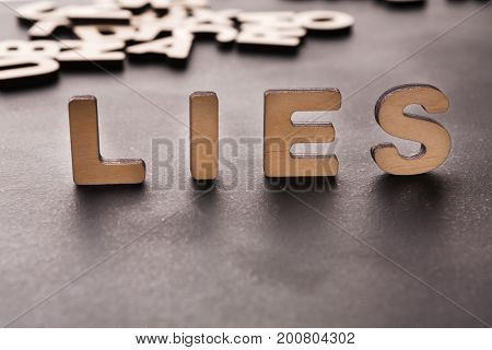 Word Lies standing on table background. Untruth, taradiddle, fake concept
