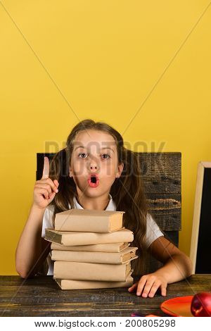 Girl Sits On Her Wooden Chair In Classroom