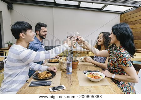 Multiethnic group of four friends toasting with their glass of wine in a restaurant