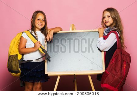 Schoolgirls With Smiling Faces Stand Near Blackboard