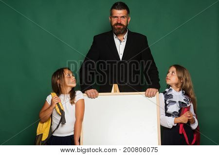 Schoolgirls Stand Near Blackboard