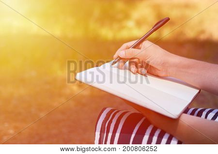 A girl writes her hand in a notebook. Study and work in the park.