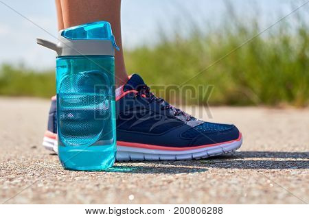 Legs of the girl in sneakers. Sports bottle with water.