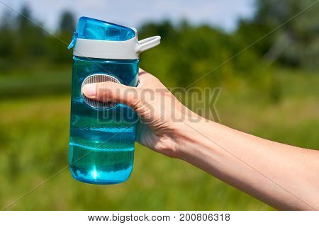 Girl hand holds a sports bottle for water.