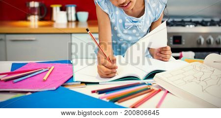 Girl drawing in book at kitchen counter