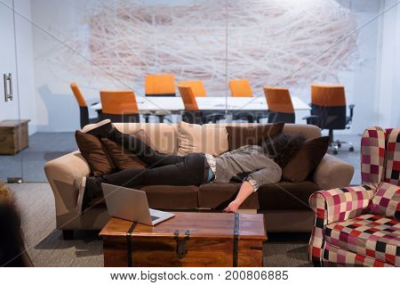 A young casual businessman sleeping on a sofa during a work break in a creative office