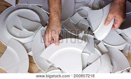 hands picking up broken white plates from wooden floor