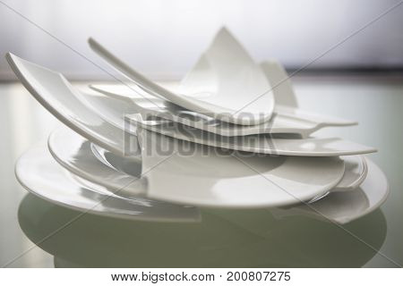 pile of broken white plates on glass table