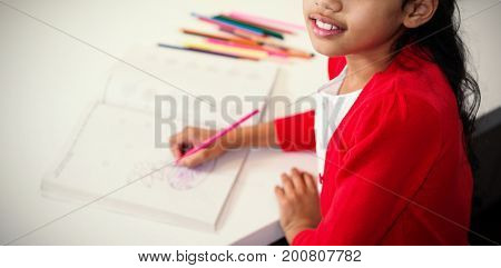 High angle portrait of girl drawing in book at table