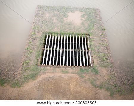 Metal Water Grid With Water Running Into It On Ground Clear