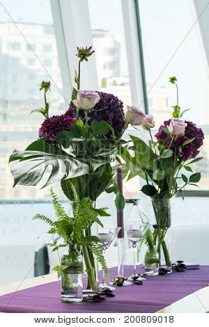 Two purple bouquets in the vases stands on the table. Beautiful violet bouquets and candles against the window. Composition of pink and violet hydrangea flowers. Beautiful floristic decor for event. Wedding decor