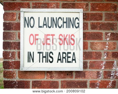 Old Retro Sign Lettering On Wall Saying No Launching Of Jet Skies In This Area