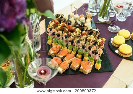 Catering service. Different canapes and cakes. Beautifully decorated catering banquet table with different food snacks and appetizers on corporate, birthday party event or wedding celebration