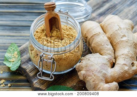 Ginger Powder In Glass Jar And Ginger Root.