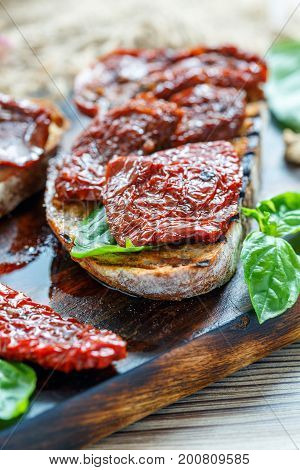 Bruschetta With Sun-dried Tomatoes And Basil Leaves.