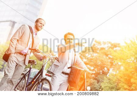 Smiling businessman with bicycle showing something to colleague on street