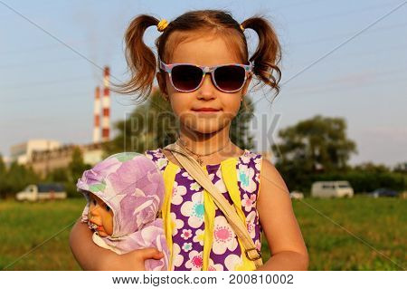 Russia, Suvorov, 08.2017: Portrait of a girl in sunglasses which play with a doll.