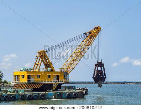 Big Crane Hanging A Rock