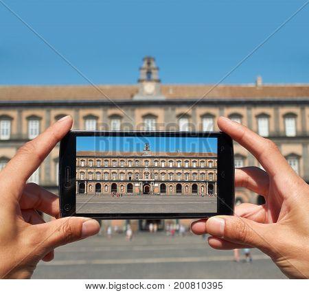 Famale hands taking a photo of Palazzo Reale di Napoli in Piazza del Plebiscito. Naples. Campania Italy.