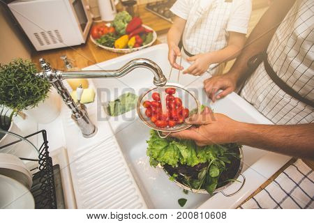 Father with little son washes vegetables on the kitchen before eating