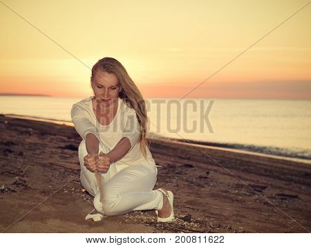 The Woman Pours Sand Hands At Sunset On The Sea.