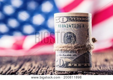 Dollars Rolled Banknotes Closeup With American Flag In The Background. Cash Money American Dollars.c