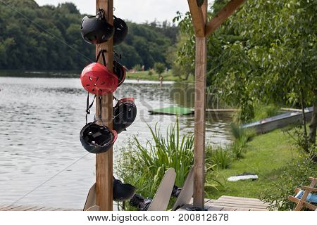 Wakeboard Helmets Hanging On A Pole Near The Lake