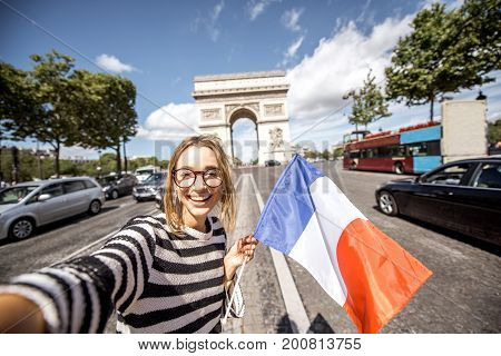 Young woman tourist with french flag making selfie portrait with famous Triumphal Arch on the background in Paris