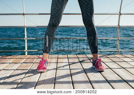 Female Legs In Sportswear And Red Sneakers