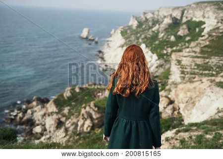 Beautiful young woman standing on a cliff of a mountain near the sea.