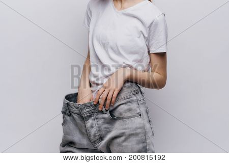 Young beautiful woman on a light background, diet, weight loss, progress, success.